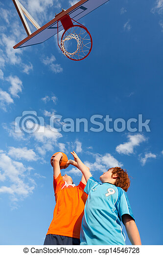 Boys Playing Basketball Against Sky - csp14546728