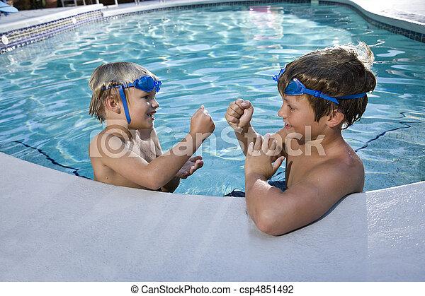 Boys playing games at edge of swimming pool - csp4851492