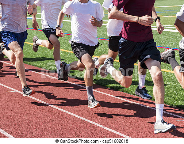 Boys running fast on a track in a group training run. A boys cross country  team running quick while in a group, on a track at | CanStock