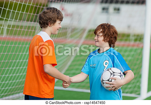 Boys Shaking Hands Against Net On Soccer Field - csp14547450