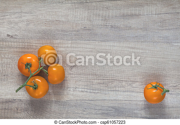Branch yellow tomatoes on light wooden surface. - csp61057223