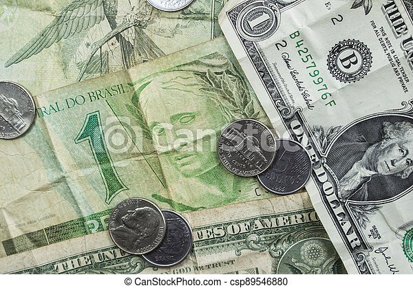 Brazilian currency and U.S. dollar bills stacked together. - csp89546880