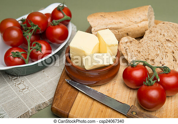 Bread and butter/Delicious organic home-made bread and butter with ripe tomatoes on wooden board - csp24067340