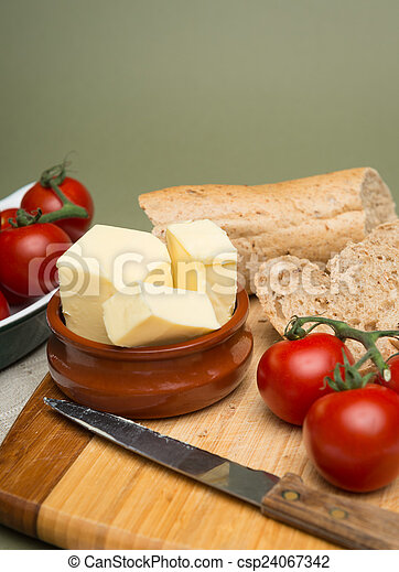 Bread and butter/Delicious organic home-made bread and butter with ripe tomatoes on wooden board - csp24067342