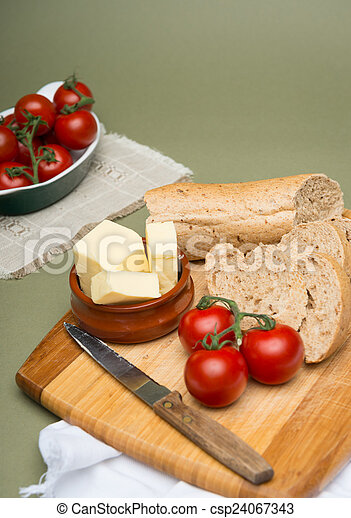 Bread and butter/Delicious organic home-made bread and butter with ripe tomatoes on wooden board - csp24067343
