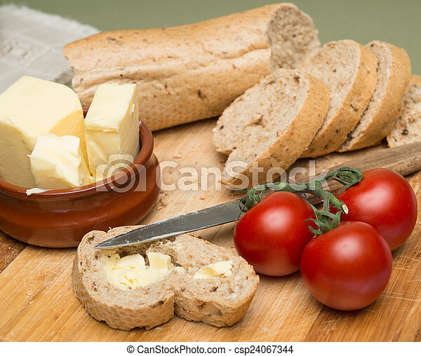 Bread and butter/Delicious organic home-made bread and butter with ripe tomatoes on wooden board - csp24067344