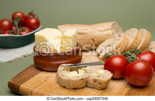 Bread and butter/Delicious organic home-made bread and butter with ripe tomatoes on wooden board - csp24067345