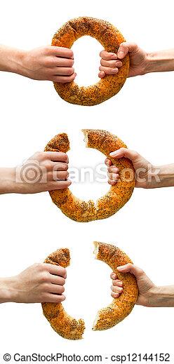 Manos quebrando pan de anillo - csp12144152