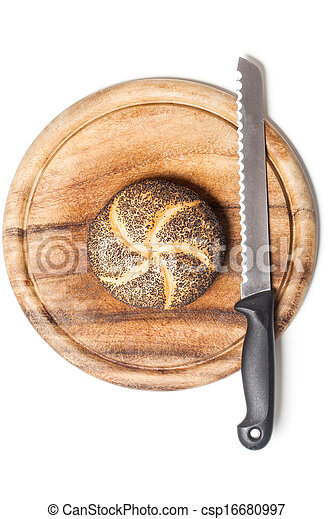 Bread roll covered with poppy seeds on cutting board with knife, typical German breakfast food. Studio shot, cutout, isolated on white background. - csp16680997