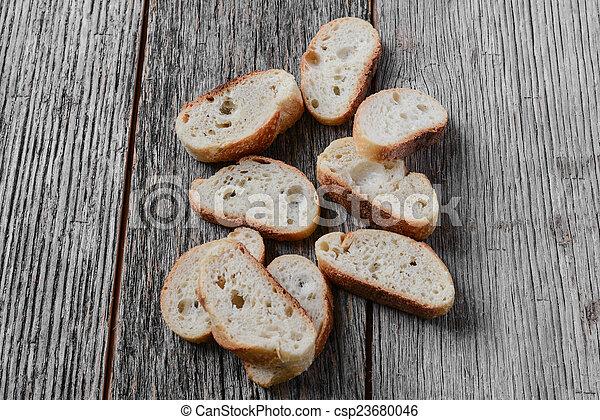 Bread Slices on Wooden Background - csp23680046