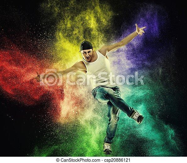 El bailarín muestra movimientos de break dance contra una explosión de polvo colorido - csp20886121