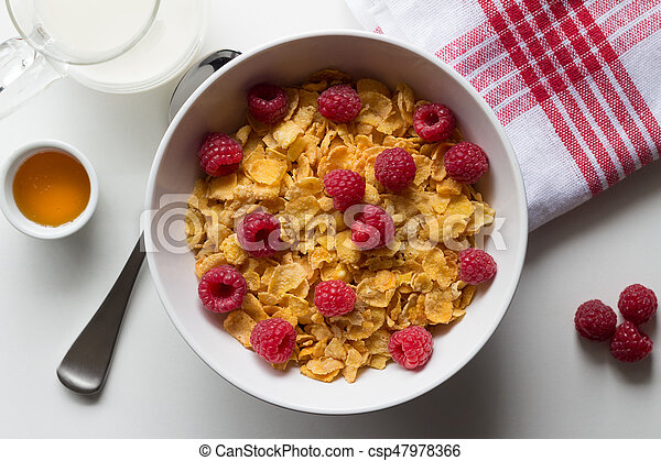 Breakfast cereal of cornflakes and raspberries, honey and milk on white table - csp47978366