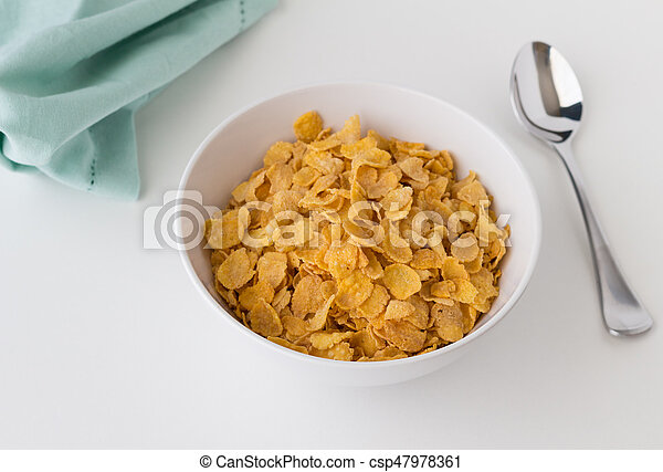 Breakfast cereal of cornflakes in bowl on white table - csp47978361