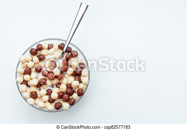 Breakfast chocolate cereal bowl with milk for morning eating. full of white and dark chocolate crispy food. - csp82577183