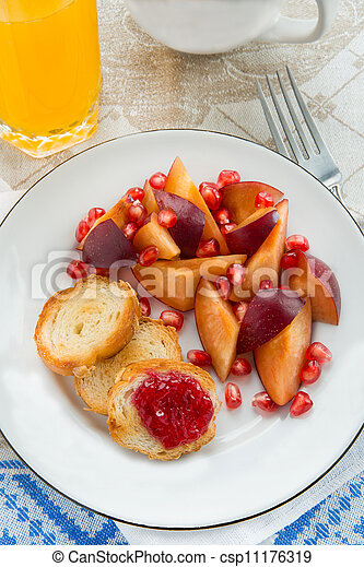 Breakfast toasts with jam, plum and pomegranate seeds - csp11176319