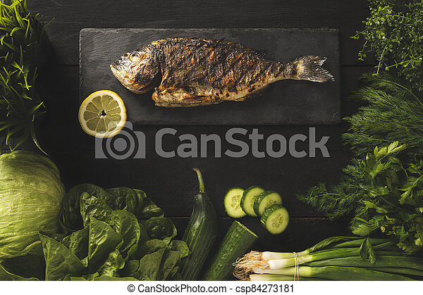 Bream fish on a black stone with green vegetables - csp84273181