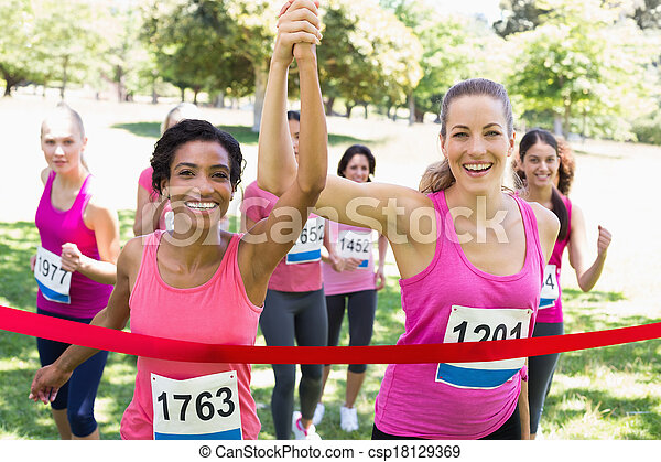 Breast cancer participants crossing finish line at race - csp18129369