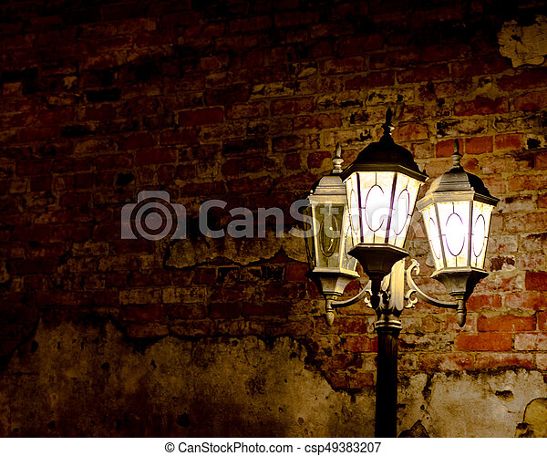 Brick wall background with illuminated street lamp - csp49383207