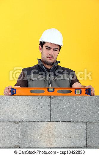 Bricklayer with a spirit level - csp10422830