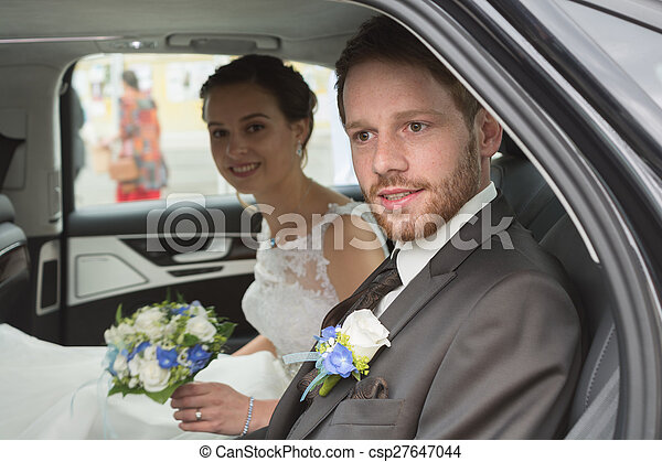 Bridal couple in the wedding car - csp27647044