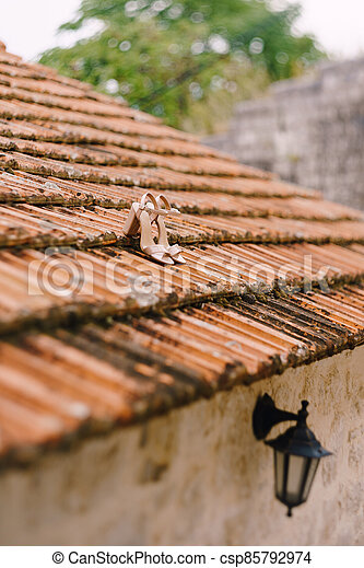 Bridal sandals on the old roof of the building with a black street hanging lamp. - csp85792974