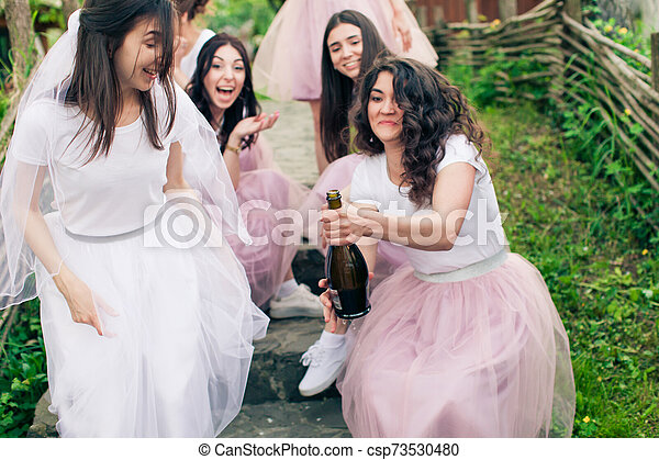 Bride and bridesmaids opening bottle of champagne, sitting on steps - csp73530480