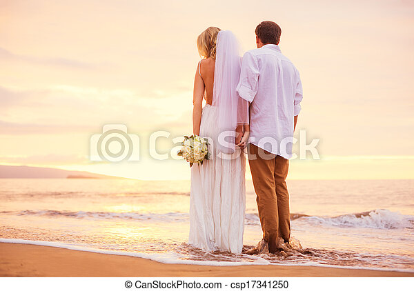 Bride and Groom, Enjoying Amazing Sunset on a Beautiful Tropical Beach, Romantic Married Couple Holding Hands - csp17341250