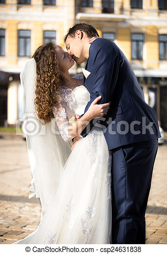 bride and groom passionately kissing on street at sunny day - csp24631838
