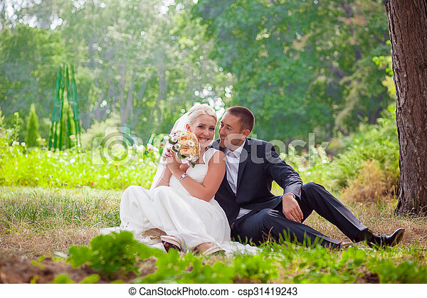 bride and groom sit on grass in the park - csp31419243