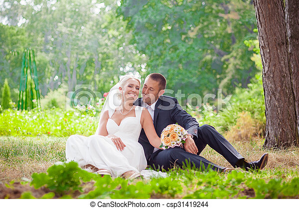 bride and groom sit on grass in the park - csp31419244