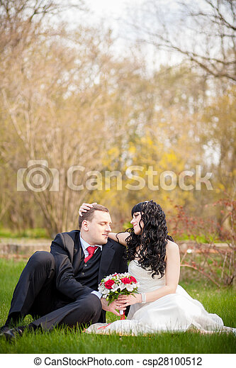 bride and groom sitting on the green grass - csp28100512