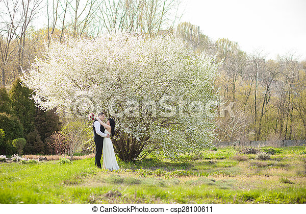 bride and groom sitting on the green grass - csp28100611