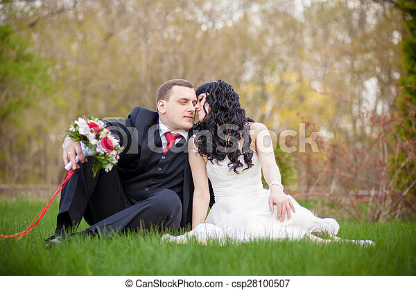 bride and groom sitting on the green grass - csp28100507