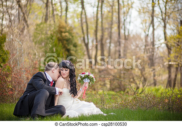 bride and groom sitting on the green grass - csp28100530