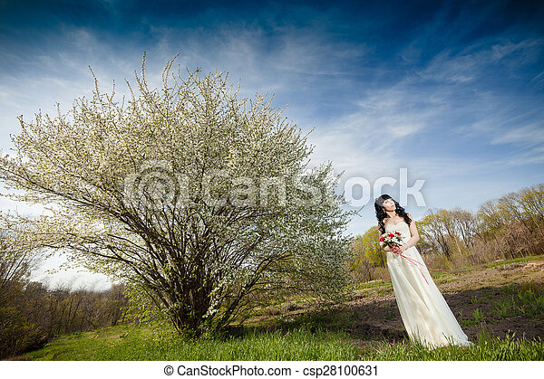 bride and groom sitting on the green grass - csp28100631