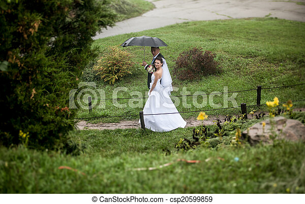 Bride and groom walking at park on rainy day - csp20599859