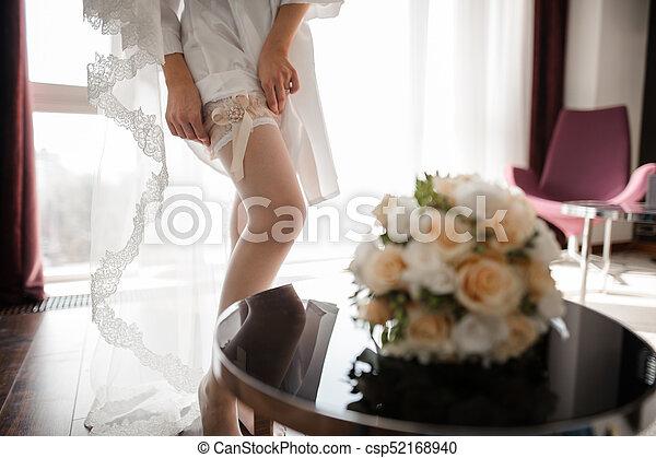 b99ae475b97 Bride dressing beautiful white stockings on feet. Bride dressing ...