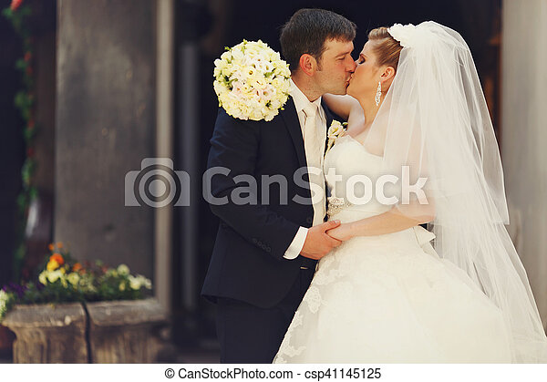 Bride holds a hand with bouquet on groom's shoulders while kissing - csp41145125