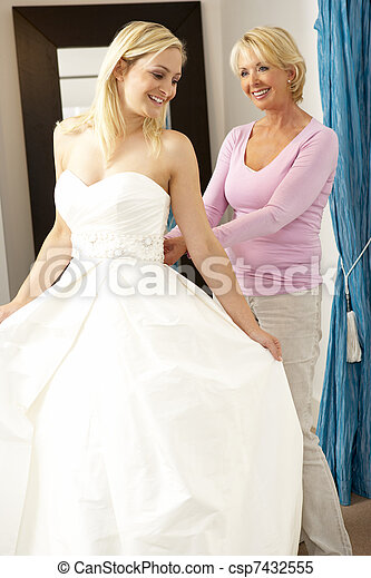 Bride trying on wedding dress with sales assistant - csp7432555