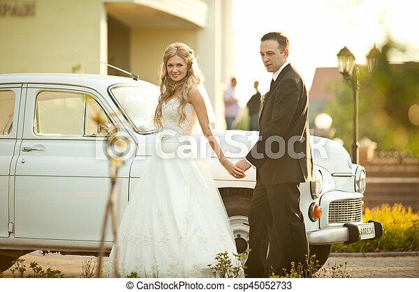 Bride walks behind an old car holding groom's hand - csp45052733
