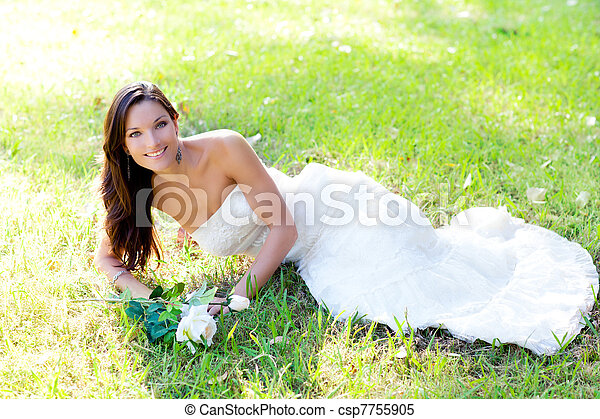 bride woman lying in park grass - csp7755905