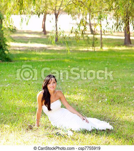 bride woman sitting in park green grass - csp7755919