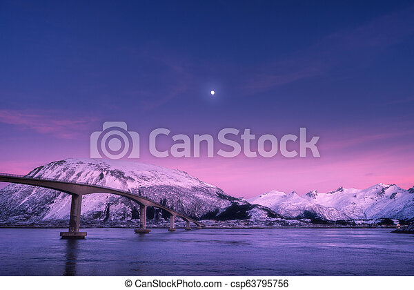 Bridge against snowy mountains, purple sky with pink clouds and moon - csp63795756