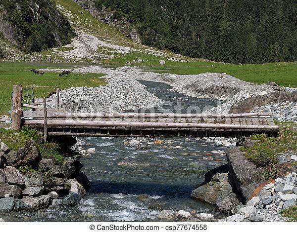 Bridge over a creek in the Alps - csp77674558