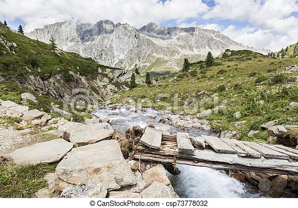 Bridge over mountain creek in Austrian/Italian Alps. - csp73778032
