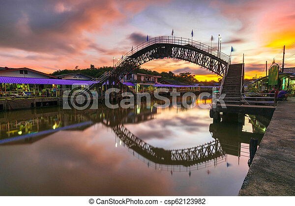 Bridge over the canal in a rural village with sunset background - csp62123982