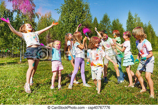 Bright and happy kids playing with colored powder - csp40767776