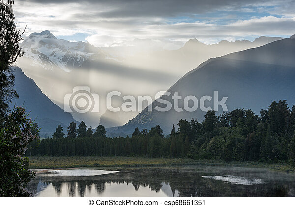 Bright contrast rays of morning sun over the Lake Matheson - csp68661351