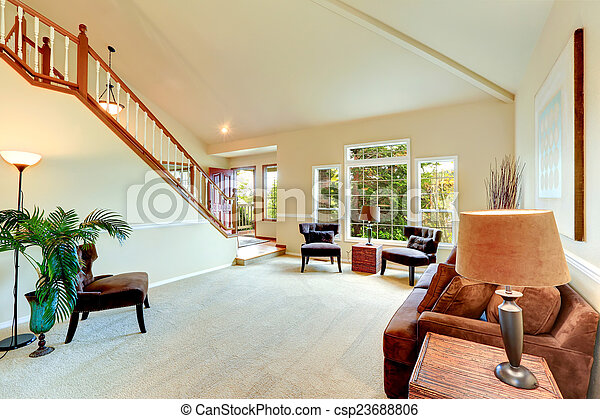 Bright ivory living room with high vaulted ceiling and french wi - csp23688806
