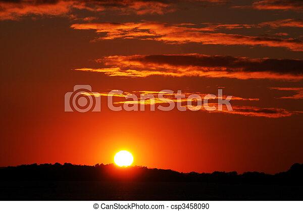 bright orange, red and yellow sunset - csp3458090
